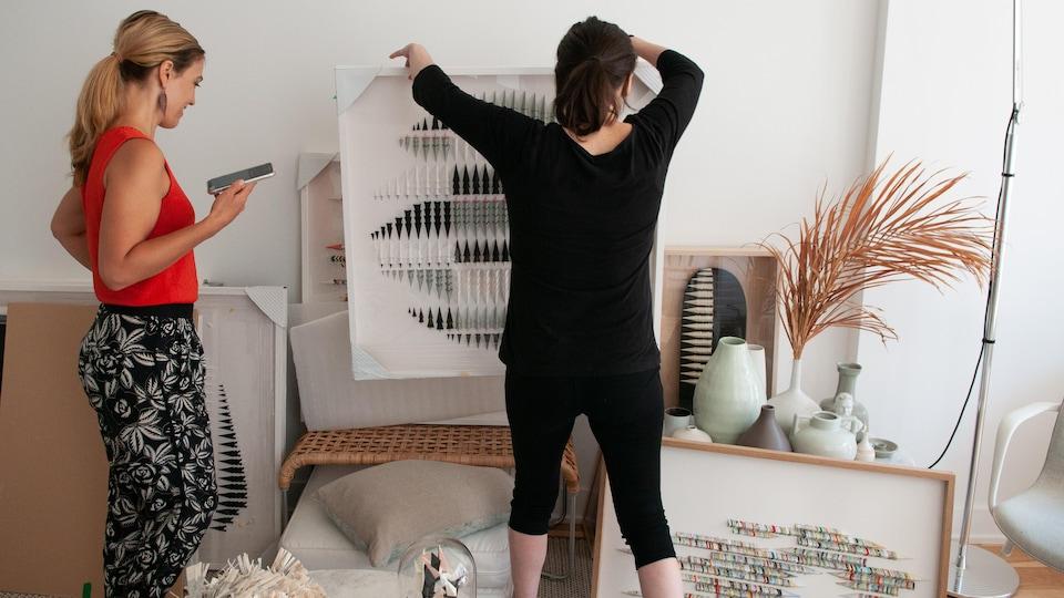 Deux femmes transportent des œuvres d'art dans un atelier blanc.