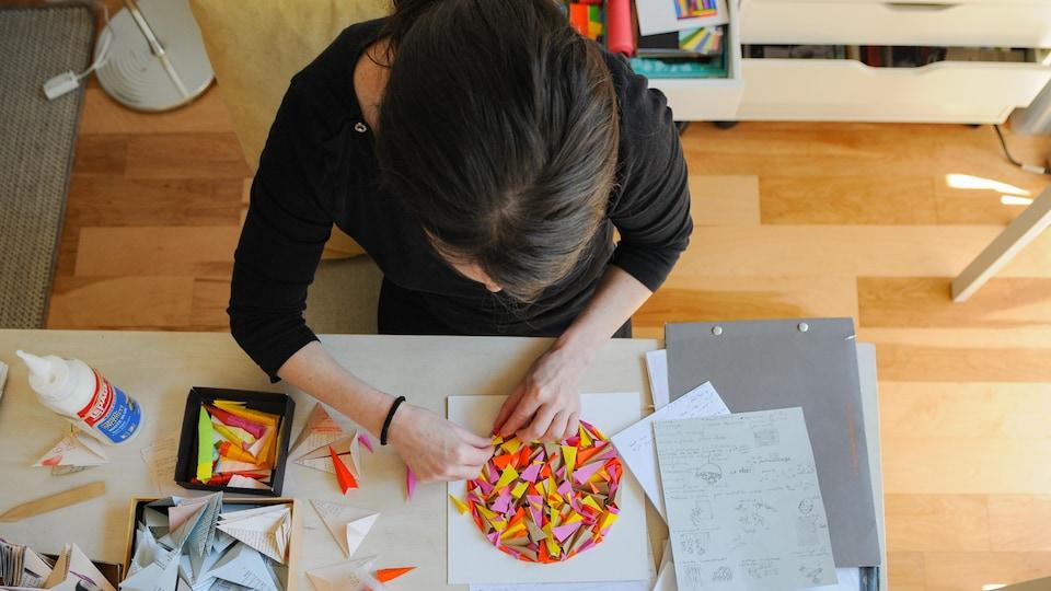 Vue de haut d'une femme en train de travailler sur une œuvre de papier sur sa table de travail dans un atelier lumineux.