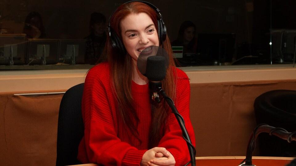 La jeune danseuse porte les cheveux rouges et un pull rouge.