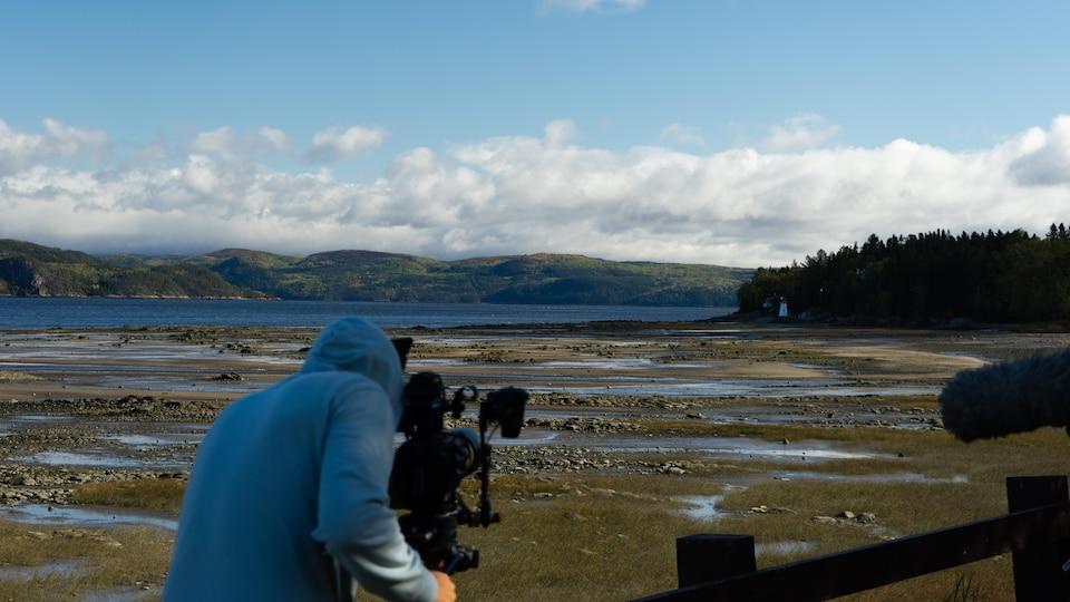 Un cameraman film un paysage de mer et montagne