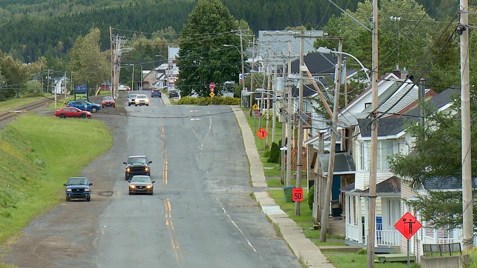 Une rue d'une petite municipalité  avec des maisons et des automobiles .