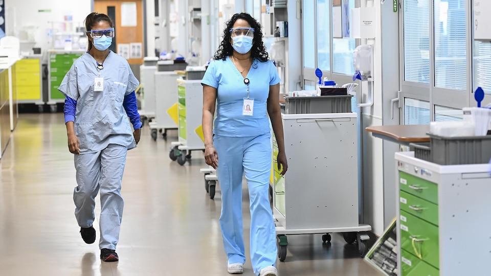 Deux infirmières avec masque et lunettes de protection marchant dans un couloir d'hôpital.
