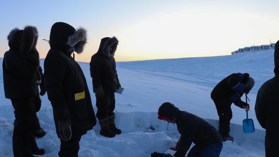 Des étudiants prélèvent des échantillons avec une pelle dans un champ de neige.