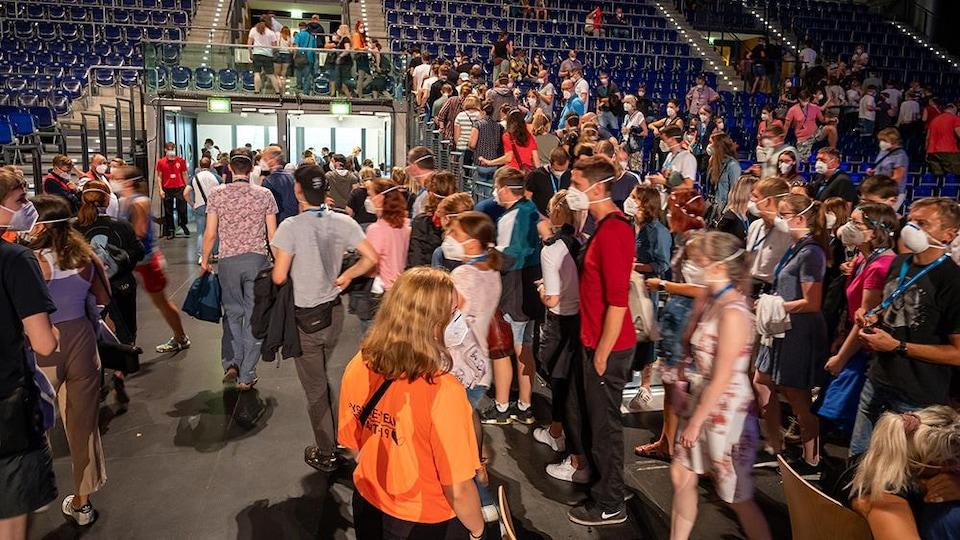 Des spectateurs dans un amphithéâtre se dirigent vers les portes de sortie à la fin d'un concert. Tous portent un masque.