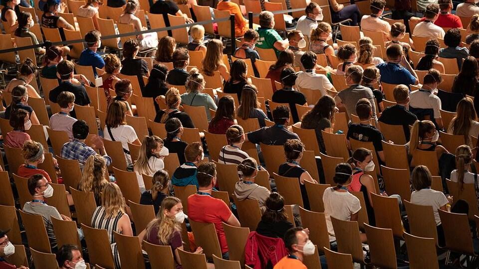 Un groupe de spectateurs sont assis dans un amphithéâtre, portant des masques. Ils sont disposés de façon à être séparés par un siège, l'un de l'autre.
