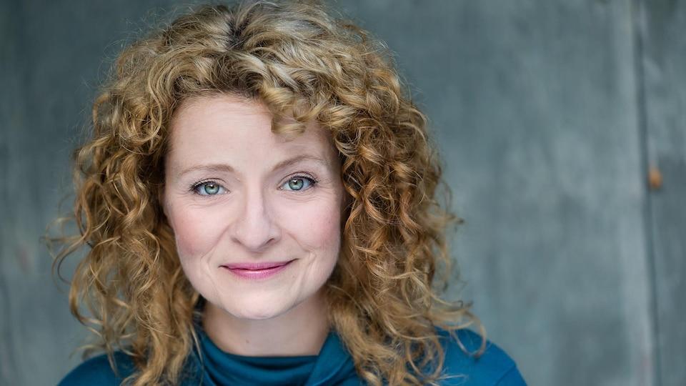 Une femme aux cheveux blonds bouclés et aux yeux bleus regardent directement vers la caméra, dans une pause de photographe professionnelle.