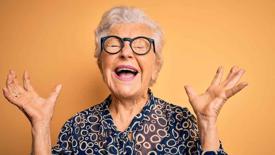 Une dame âgée, aux cheveux gris et portant des lunettes à la mode, s'exclame les yeux fermés, dans la joie.