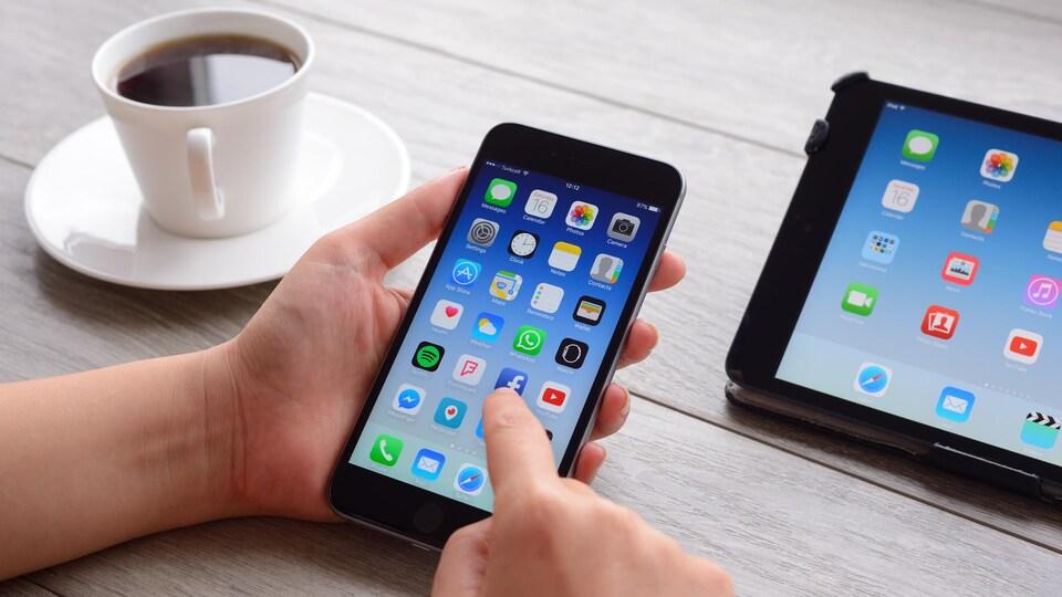 Une personne s'apprête à sélectionner une icône sur son téléphone intelligent.
