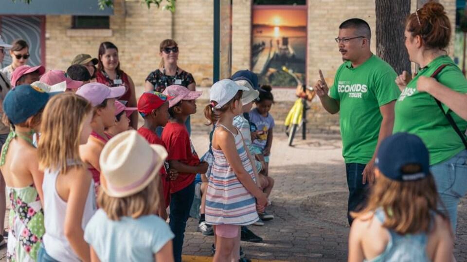 Un comédien vêtu d'un chandail vert, évoquant l'écologie, parle à un groupe d'enfants réunis sous un arbres près d'un édifice public.
