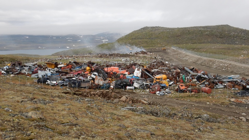 Une montagne de déchets, de ferrailles et de contenants variés encombre l'avant-plan d'un vaste paysage qui descend vers une rivière.