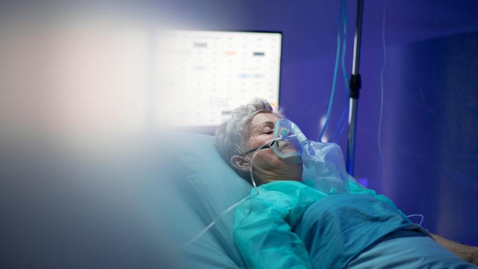 Une patiente, avec un masque à oxygène, couchée dans un lit d'hôpital.