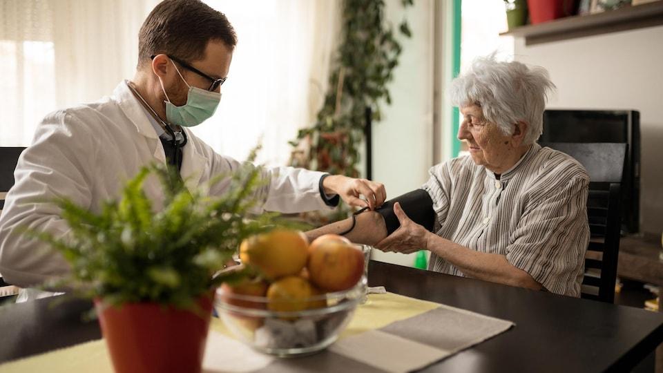 Un infirmer portant un masque mesure la pression artérielle d'une personne âgées à l'aide d'un brassard de tensiomètre.