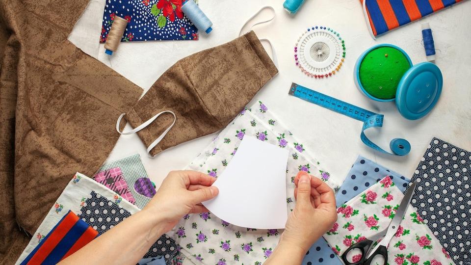 Plusieurs tissus différents et du matériel de couture pour la fabrication de masques maison.