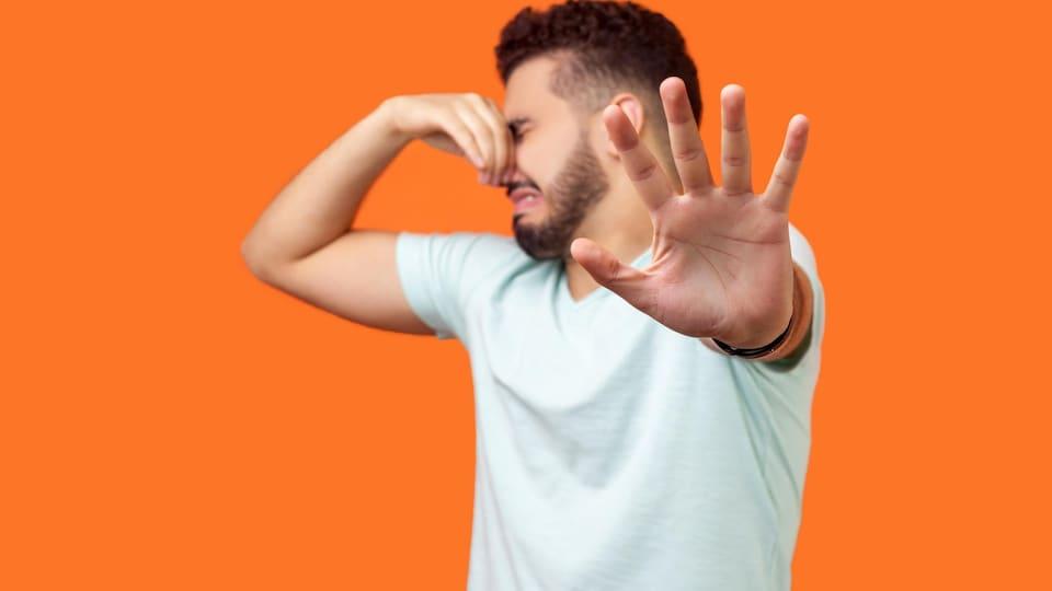 Un homme se pince le nez en raison des mauvaises odeurs.
