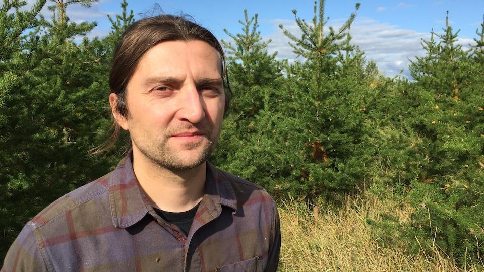 Un homme à la chevelure longue et attachée pose en plein soleil devant une petite forêt de pins gris en pleine croissance.
