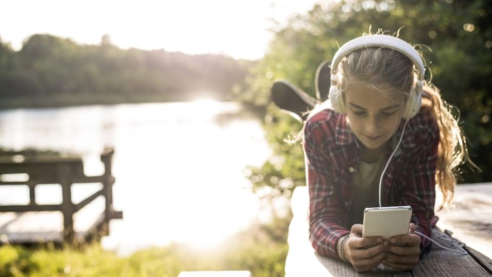 Une jeune fille est plongée dans son cellulaire, en pleine nature.