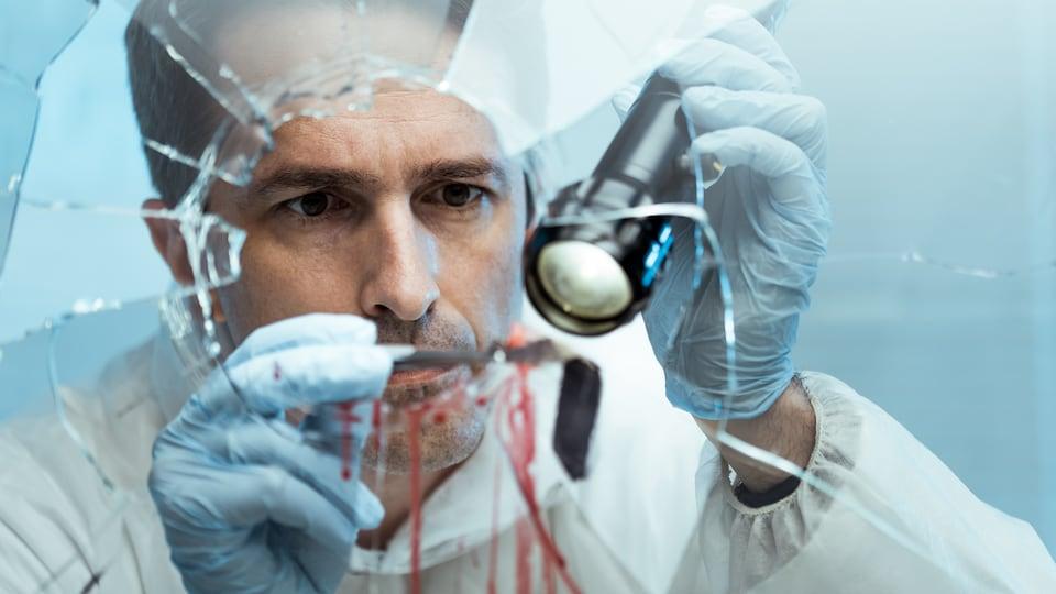 Un scientifique collecte des éléments de preuve sur une vitre brisée.