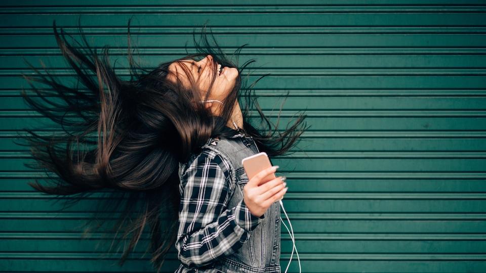 Jeune femme qui écoute de la musique, cheveux au vent.