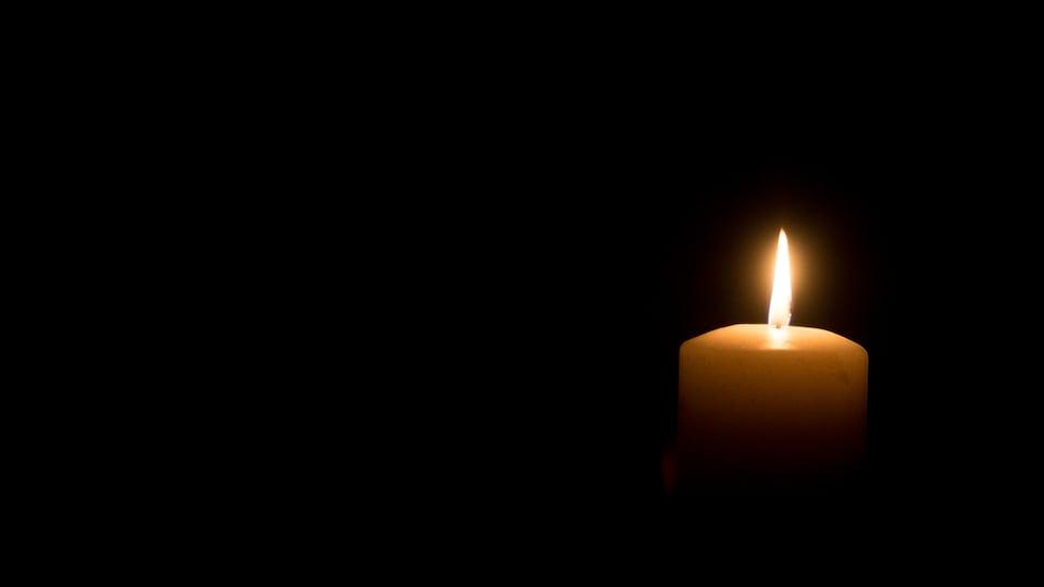 Un chandelle brûle dans le noir.