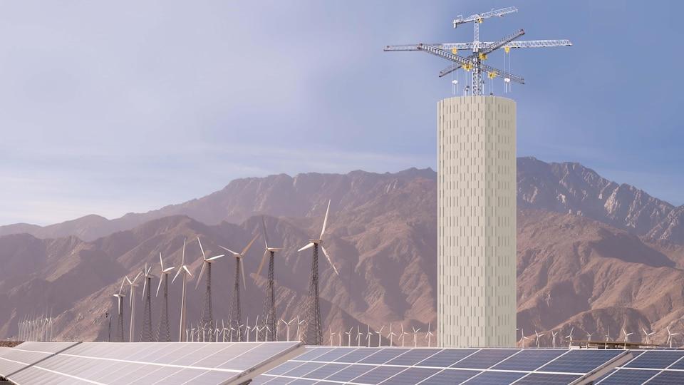 Une immense tour de blocs de béton est assemblées à proximité d'un parc éolien et solaire.