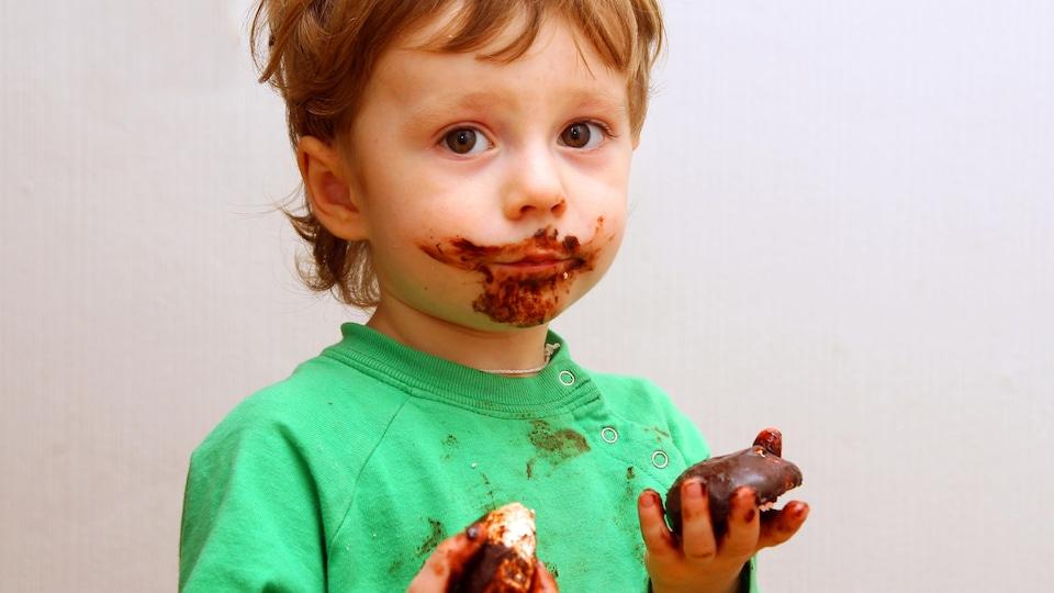 Un garçon avec la figure barbouillée de chocolat.