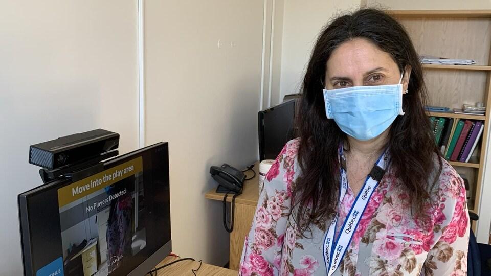 Une dame à la longue chevelure noire, portant un masque de procédure bleu, pose pour la caméra, debout, devant un écran d'ordinateur.