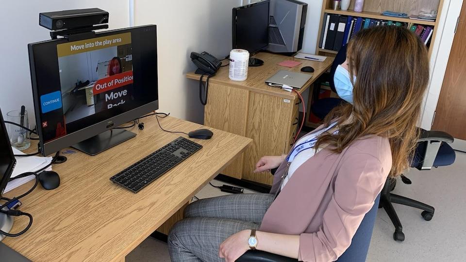Une jeune femme à la longue chevelure brune, portant un masque, est assise devant un écran d'ordinateur qui est équipé de divers instruments vidéo.