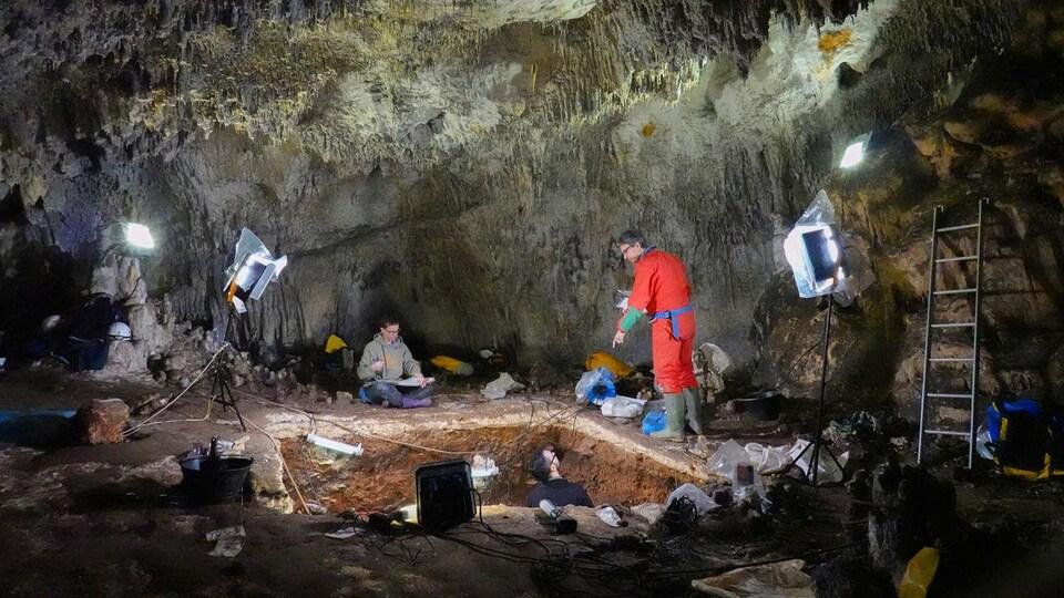 Des chercheurs excavent des sédiments d'une tranchée dans une caverne.