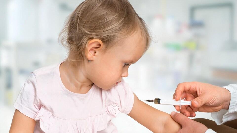 Une fillette se fait vacciner sur le bras.
