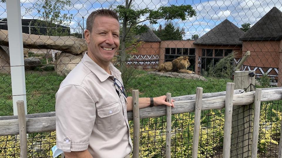Un homme souriant, en uniforme, s'appuie sur une clôture, devant un enclos grillagé où se repose un lion, dans un zoo.
