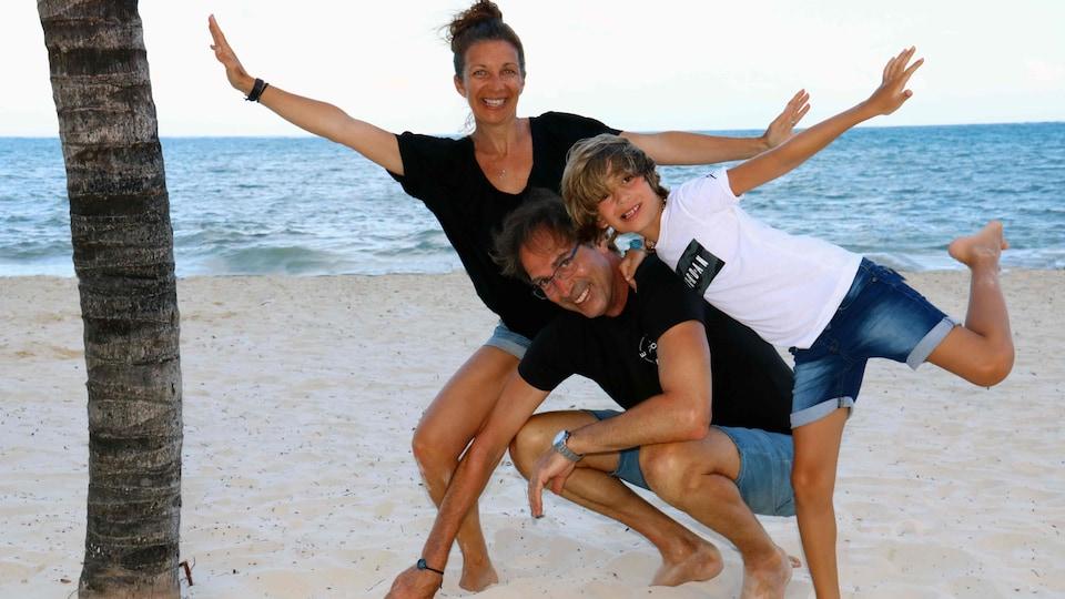La famille Taschereau-Miron pose sur une plage près d'un palmier