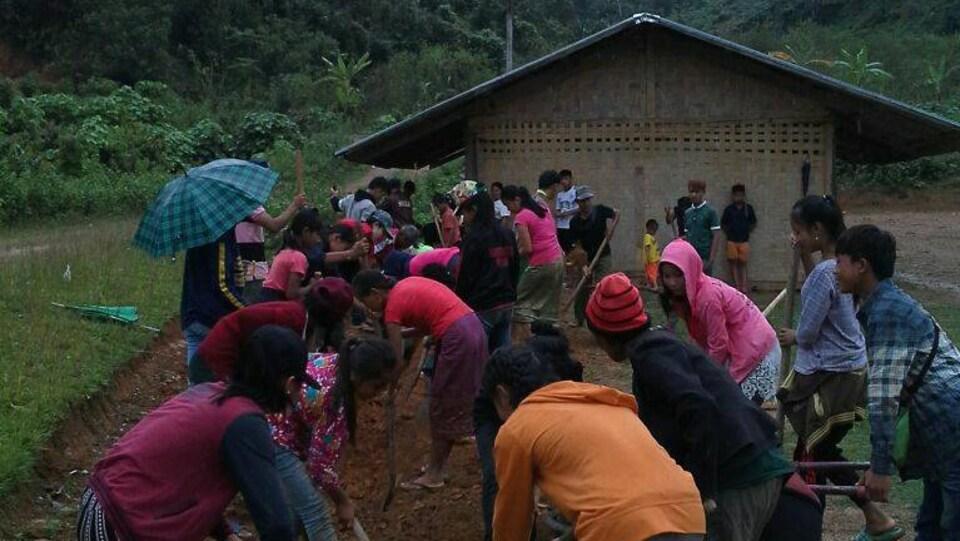 Des jeunes creusent dans la terre une rigole au Laos.