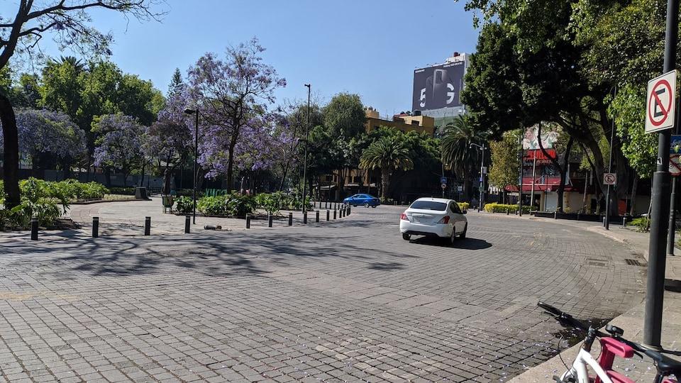 Une place urbaine désertée avec une seule voiture sur la route.