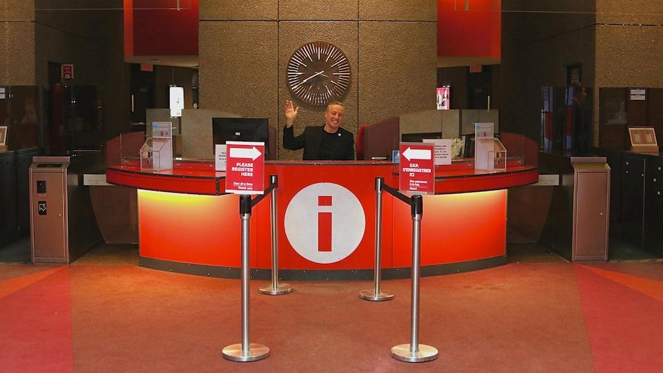 Robert Houle, assis derrière le bureau de l'accueil, salue avec sa main en souriant.