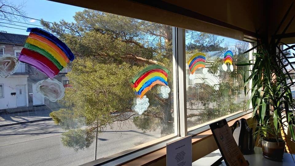 Des arcs-en-ciel peints dans les fenêtres d'une résidence.