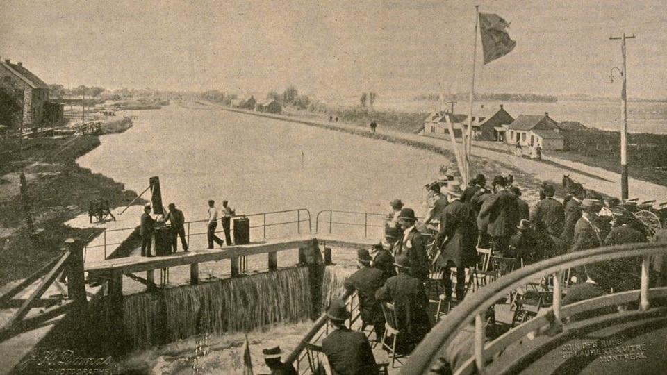 Image d'époque montrant des personnes sur le pont d'un bateau voguant sur un canal.