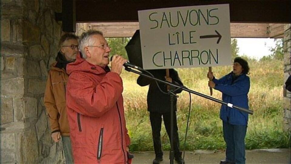 Des personnes manifestent; l'une d'elles tient une pancarte disant «Sauvons l'île Charron».
