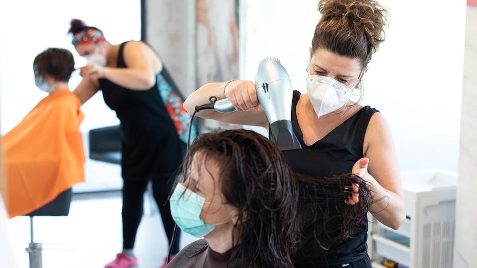 Deux coiffeuses portant des couvre-visages sont au travail dans un salon de coiffure.
