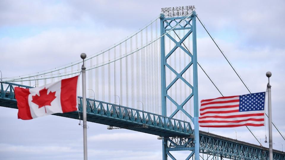 Des drapeaux flottent devant le pont Ambassador et la frontière canado-américaine à Windsor, en Ontario.