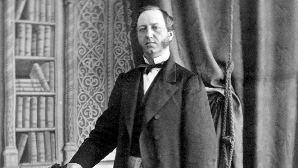 L'honorable Pierre-Joseph-Olivier Chauveau, debout devant une chaise, chapeau haut-de-forme à la main.