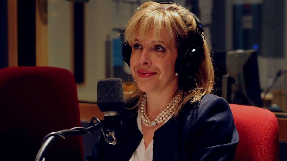 Une femme, avec un collier de perles au cou et des écouteurs sur la tête, est assise devant un micro.