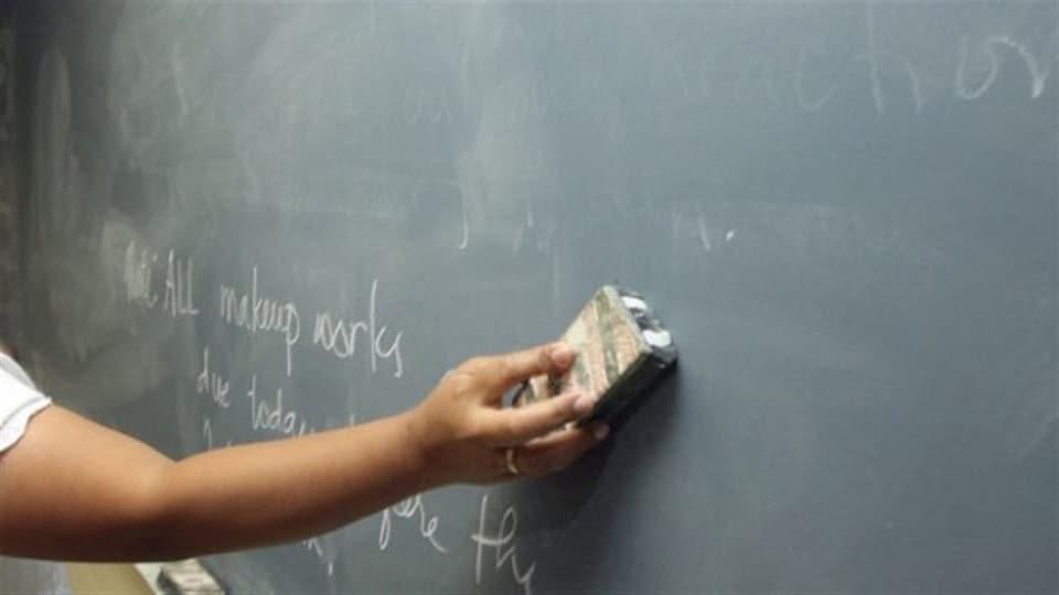 La craie sur un tableau est effacée dans une classe.