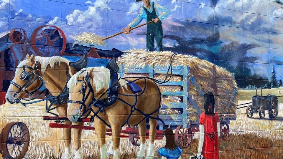 Peinture murale de Legal représentant des femmes qui apportent de la nourriture à un fermier debout sur une carriole remplie de foin.