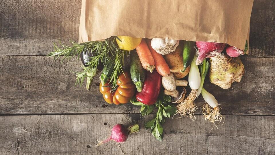 Des légumes frais dépassant d'un sac renversé sur une table.