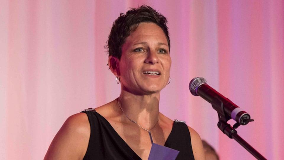 Une femme est sur une scène devant un micro et papiers dans les mains, fait ses remerciements.