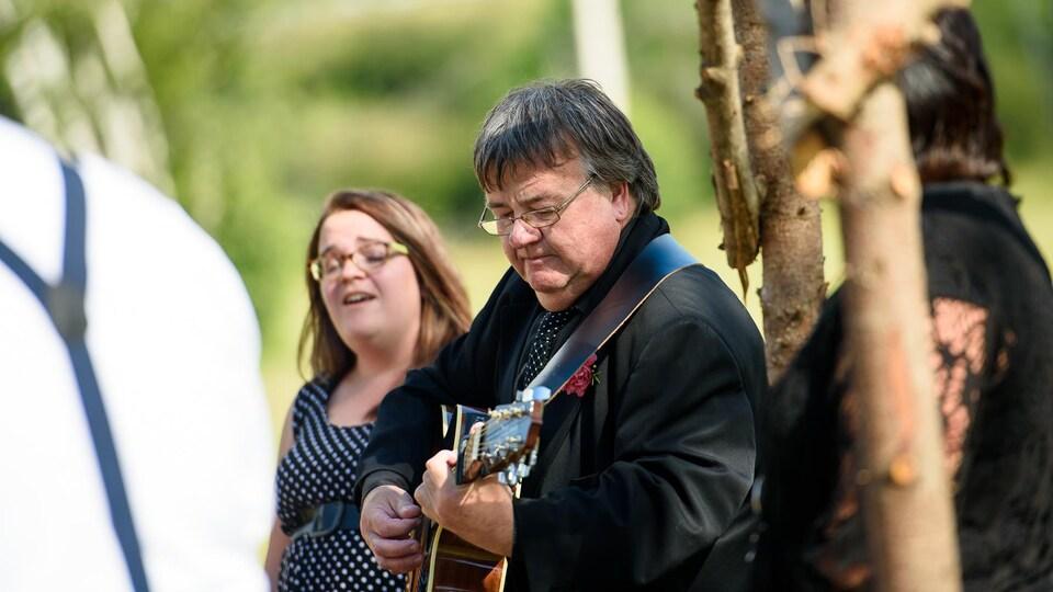 Paul Gallant accompagne à la guitare sa fille Adrienne, qui chante à un mariage en plein air.