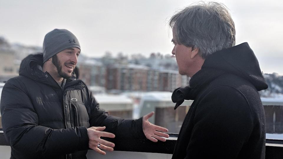 Un homme parle à un autre qui l'écoute; les deux sont à l'extérieur en hiver.