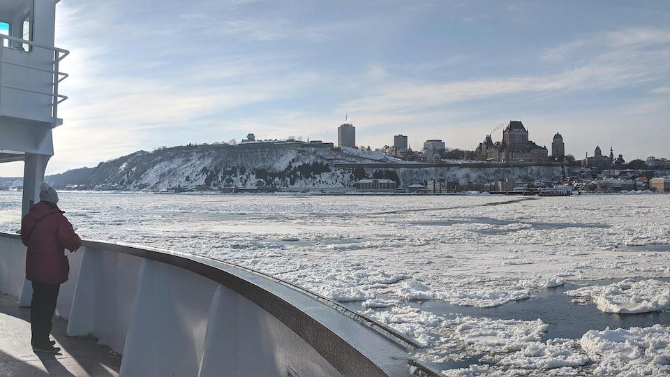 Sur un traversier en hiver sur un fleuve gelé, une personne regarde une ville au loin.