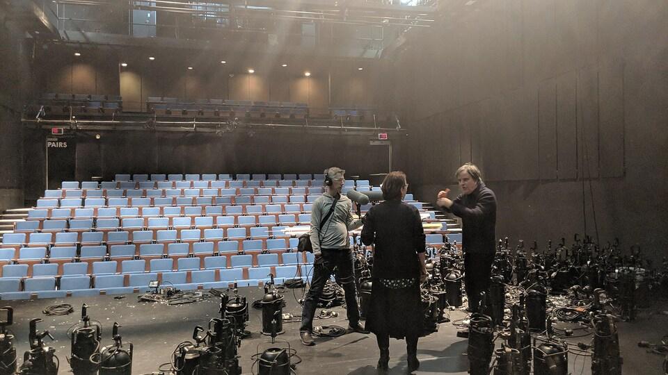 Sur une scène de théâtre jonchée d'équipements d'éclairage, un homme tient des micros, une femme est de dos et un autre homme lui parle.