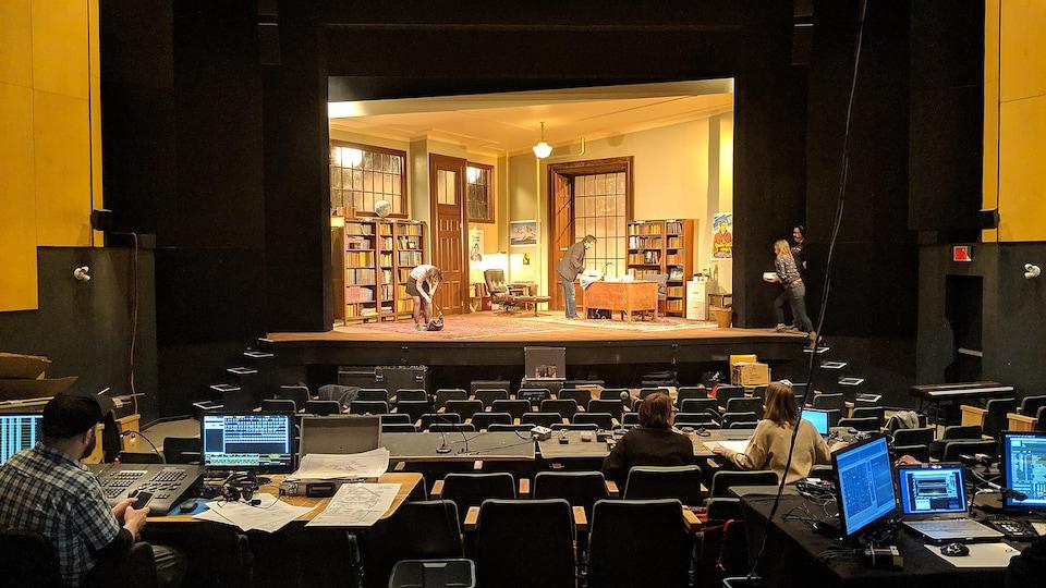 Une actrice et un acteur sont sur une scène de théâtre; deux personnes sont sur le côté droit de la scène. Dans la salle, trois personnes les regardent.